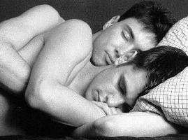 [B&w photo of two young men sleeping in embrace]
